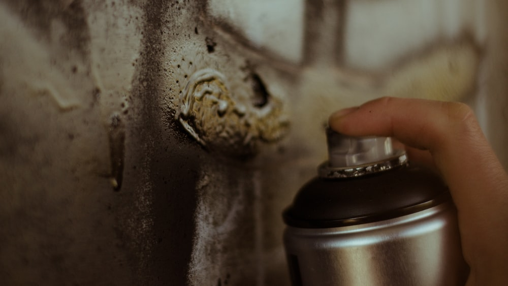 person holding gray spray can