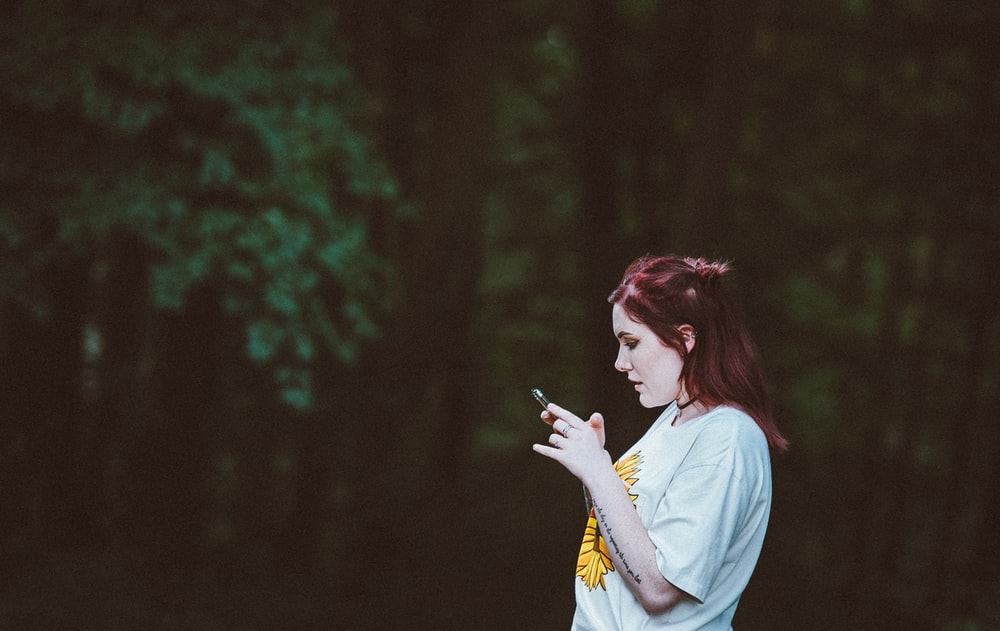 selective focus photography of woman staring on her phone