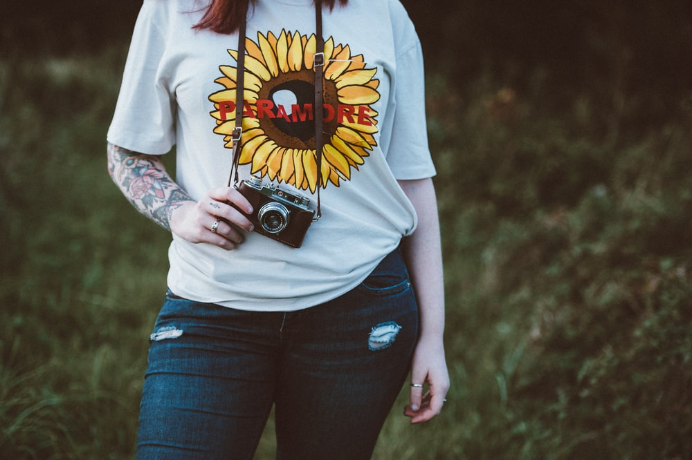 woman holding SLR camera standing near grass