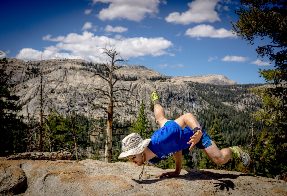 man doing hand stand on edge of cliff