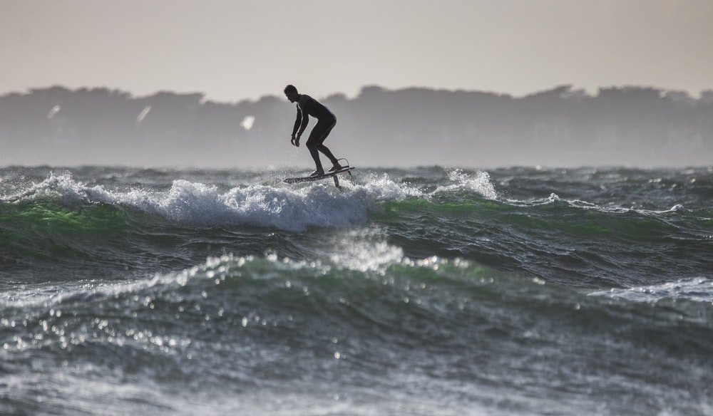 time lapse photography of man riding surfboard