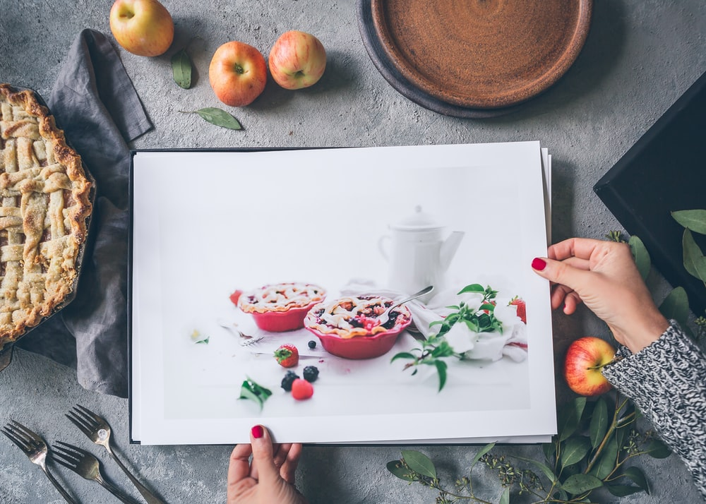 person holding painting beside apples