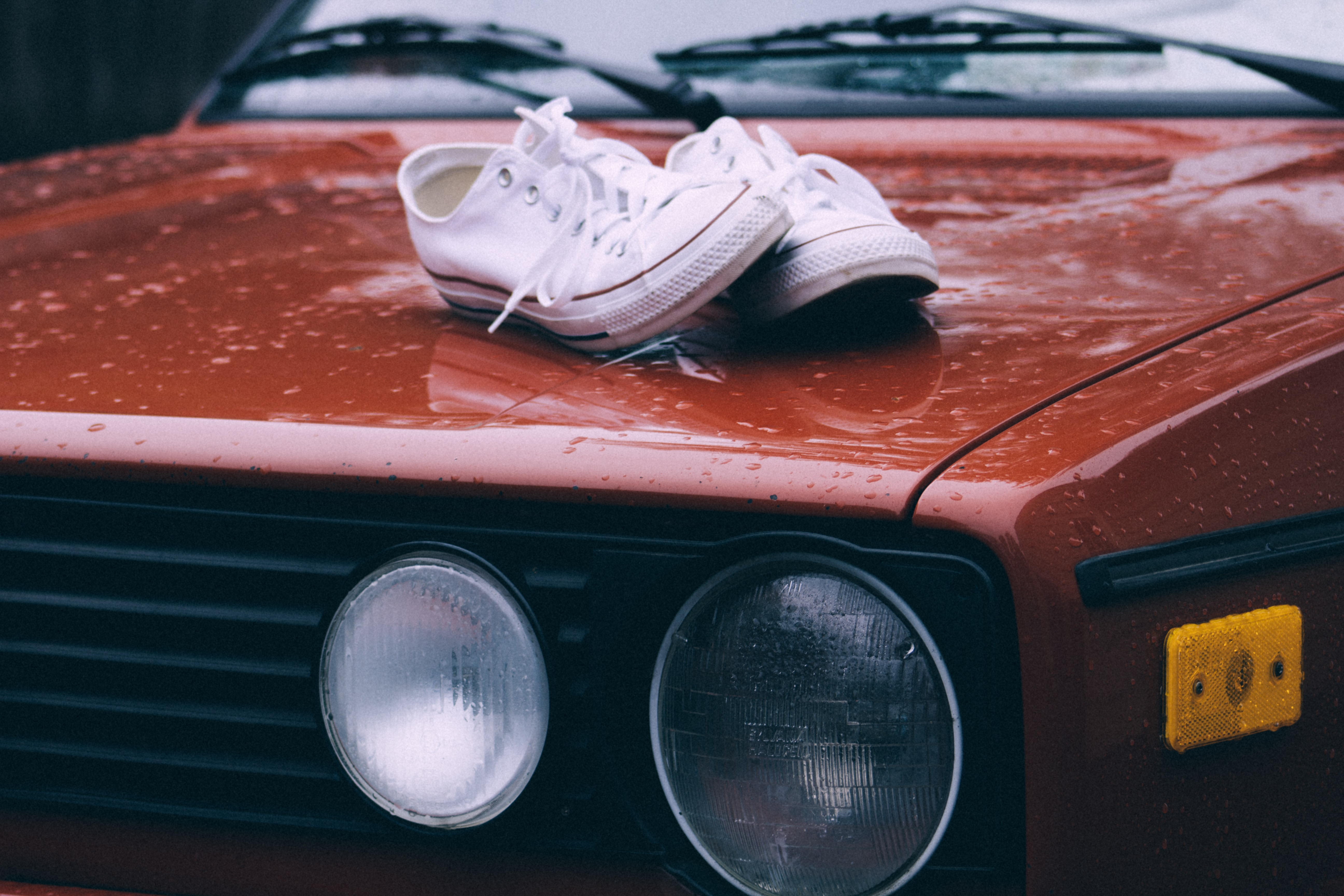 show low-top shoe on red car hood