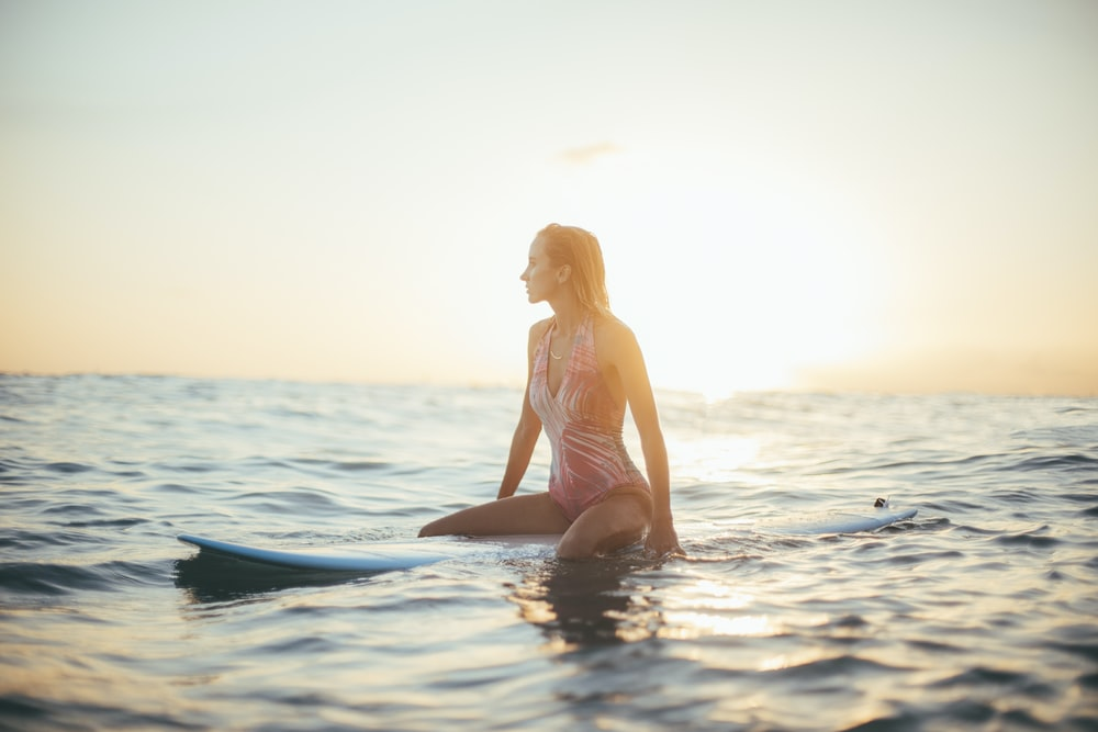 woman riding a blue surfboard in a body of water