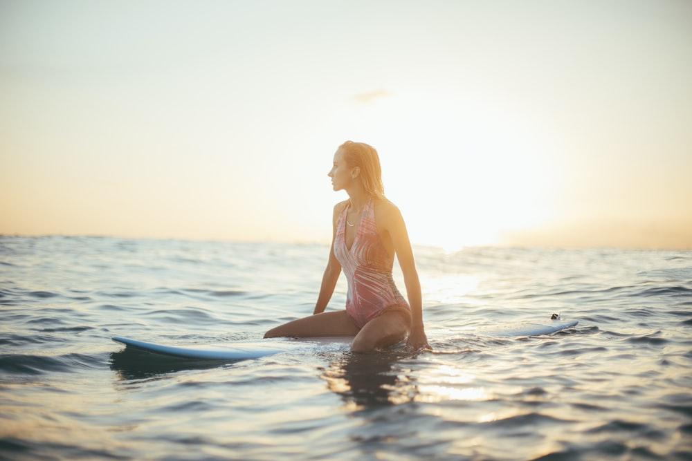 woman riding a blue surfboard in a body of water pattaya beach