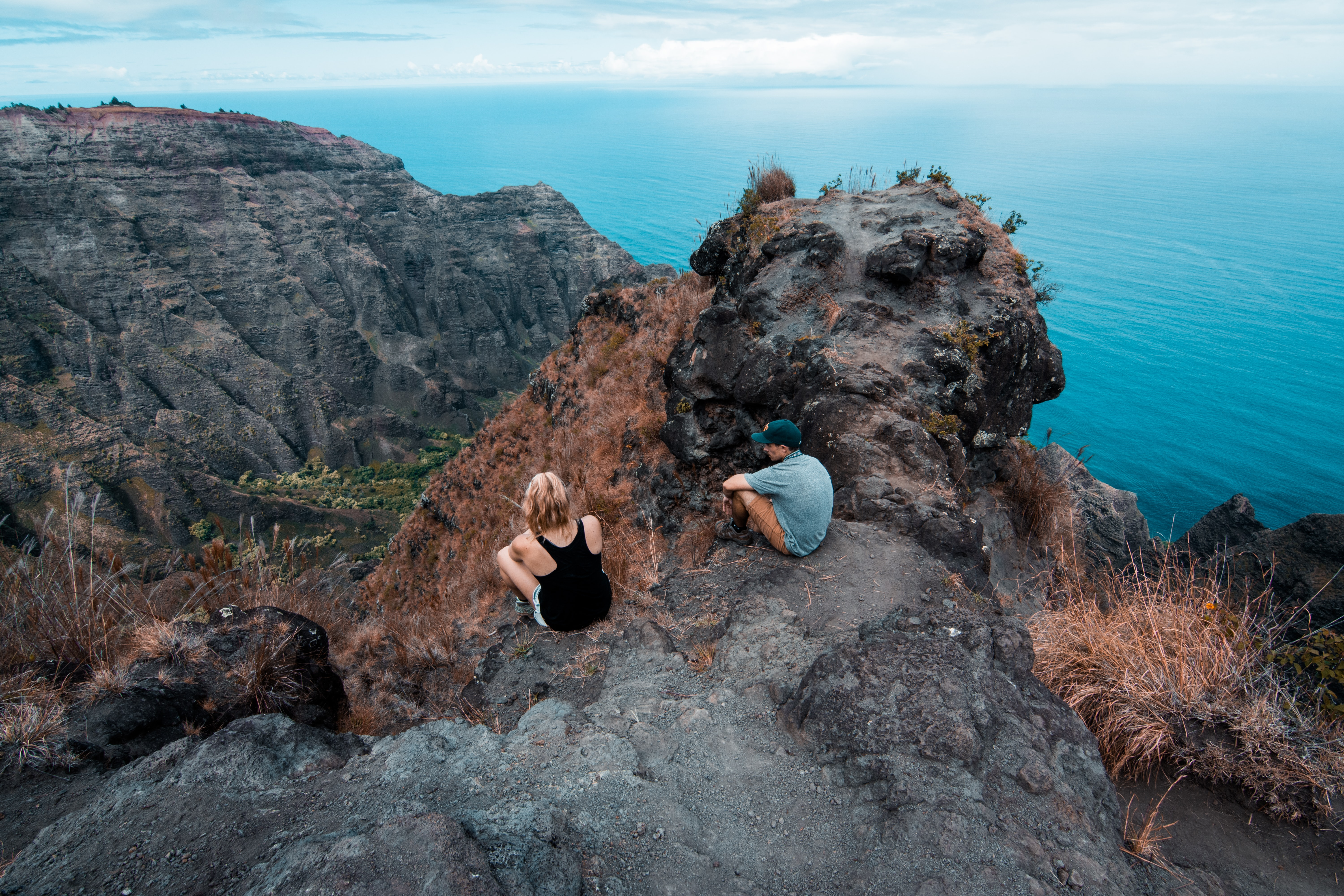 man and woman seating on mountain during day time
