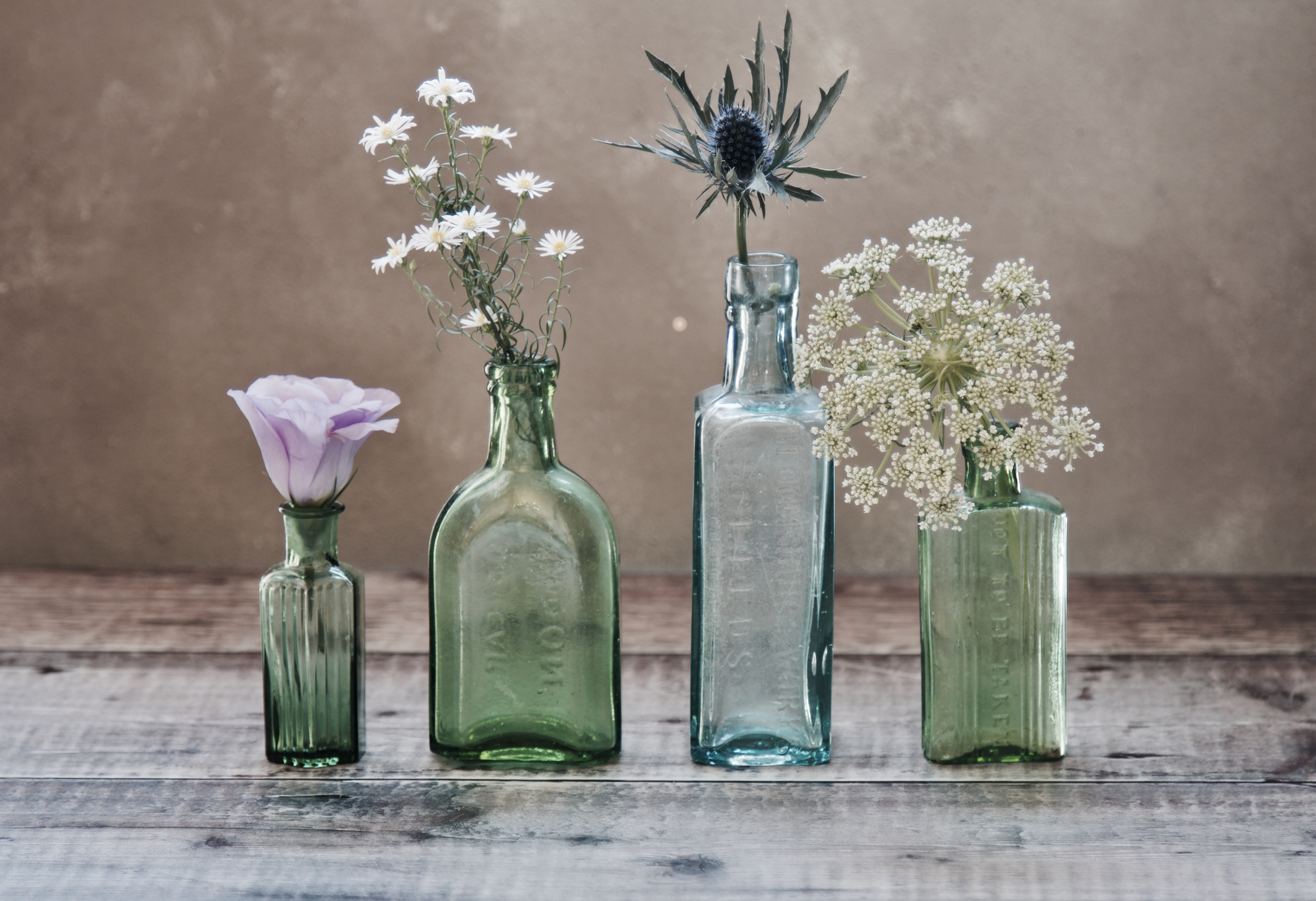 three green and one blue glass vases with flowers inside