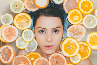 woman surrounded by sliced lemons beauty teams background
