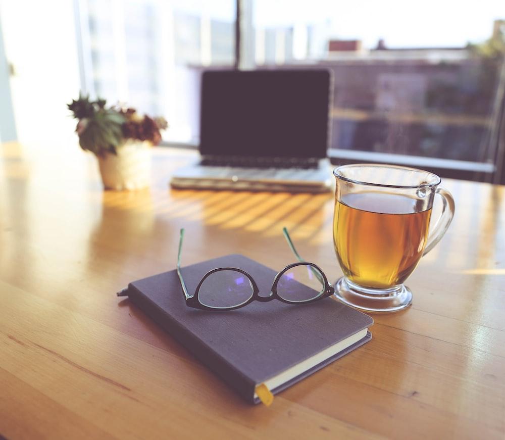 clear eyeglasses on top of black book beside clear glass mug