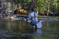 man fishing river at daytime