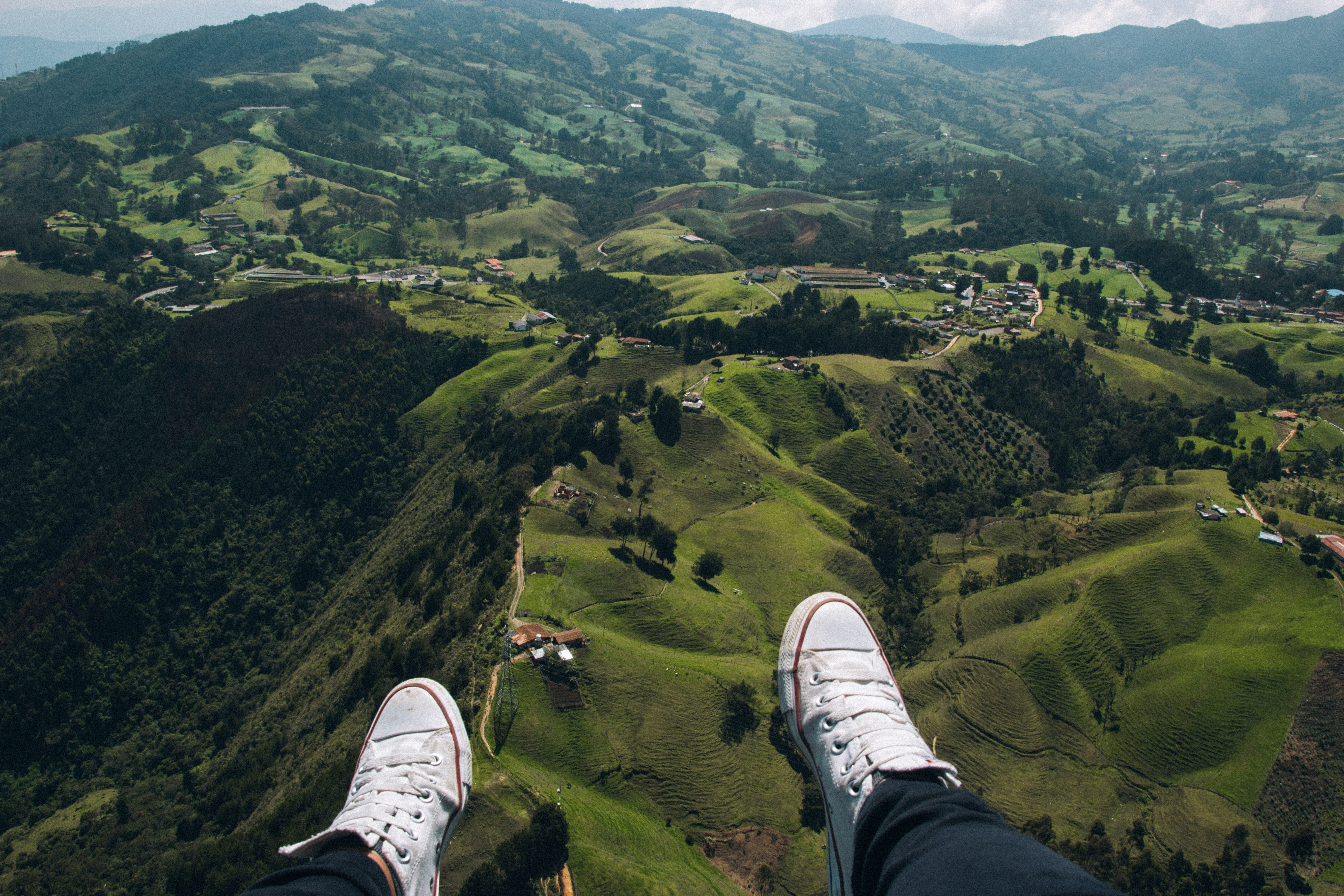 person in white sneakers facing aerial view of green mountain and houses