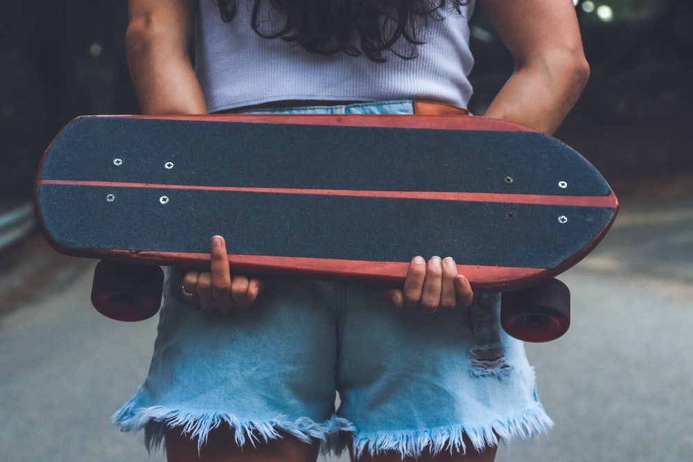 woman holding brown and black skateboard
