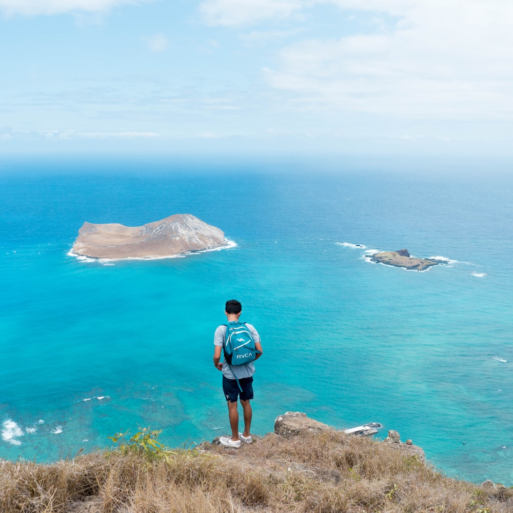 man carrying blue backpack while standing on brown cliff near body of water during daytime