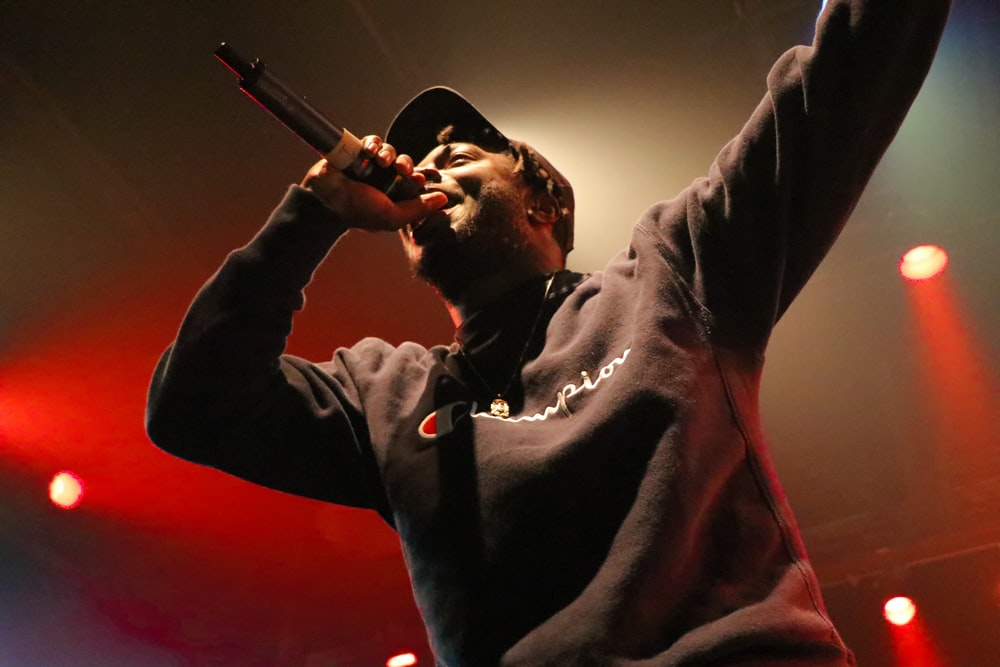black holding microphone and singing on stage