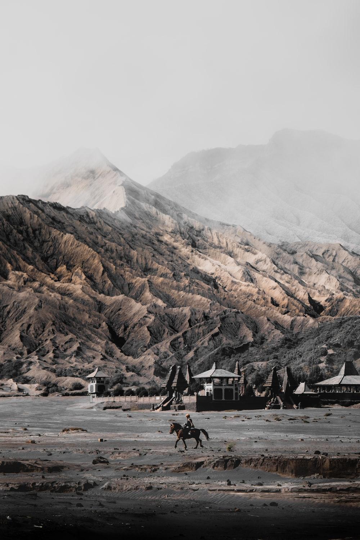 person riding horse near mountain range