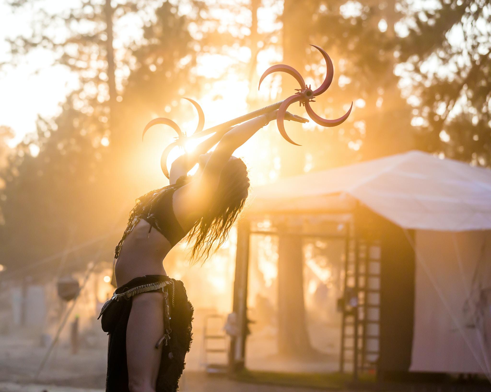woman lifting metal bar near white tent