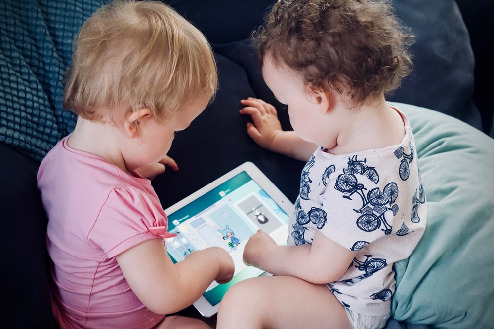 two toddlers sitting on sofa while using tablet computer