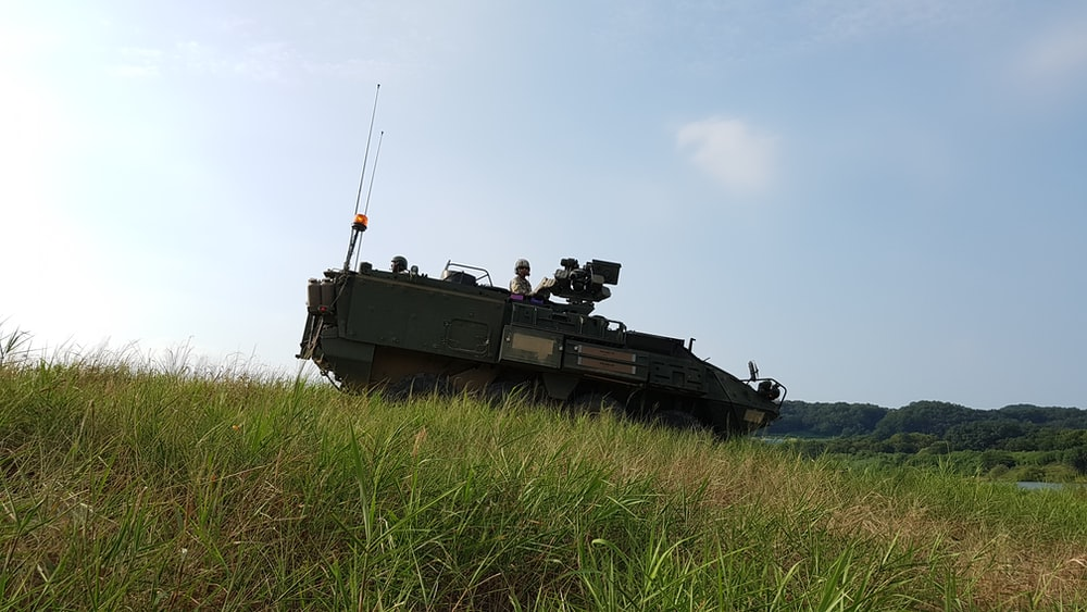 green army tank parking on green grass ground