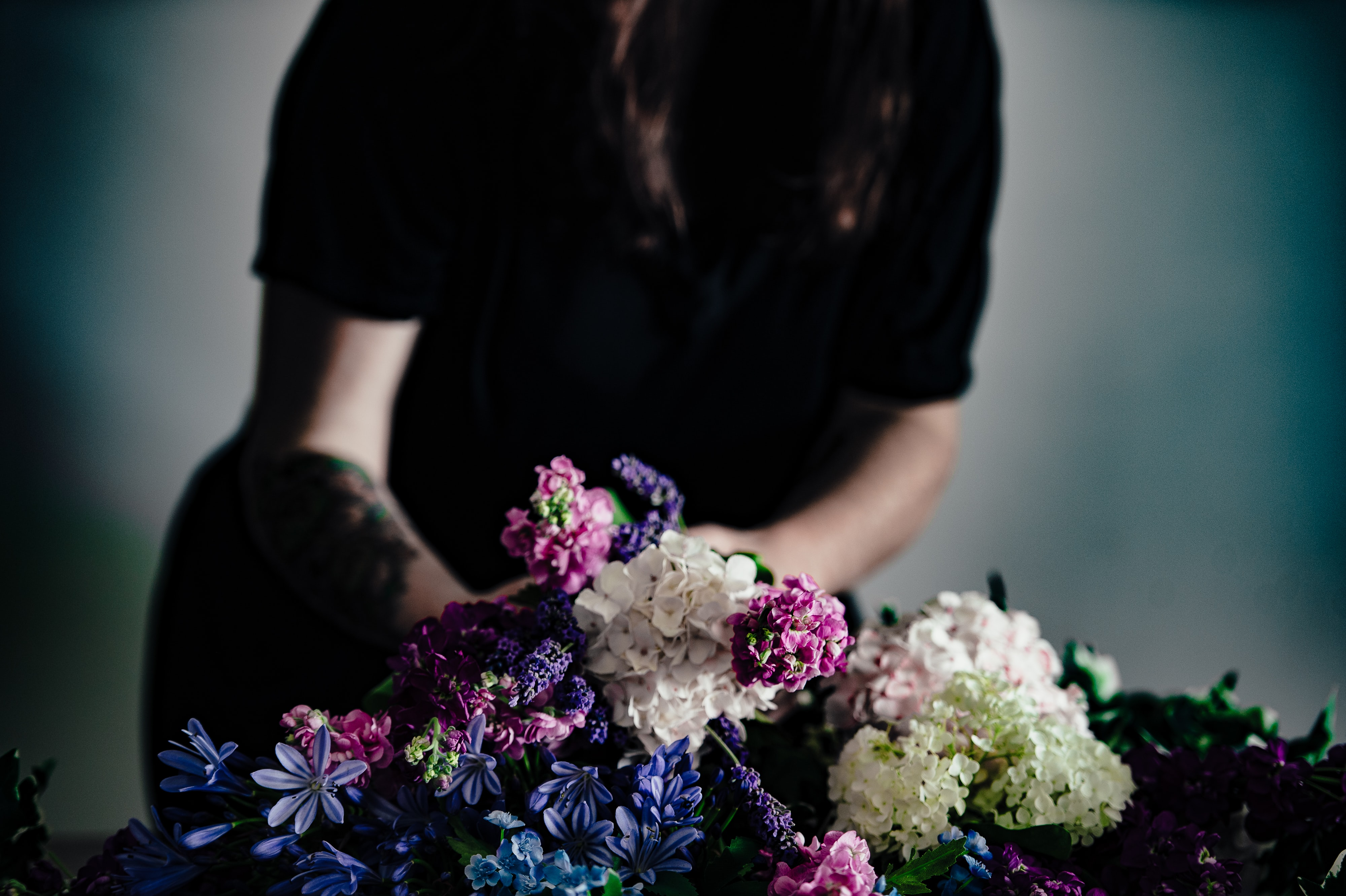 white and pink flower bouquet in front of man