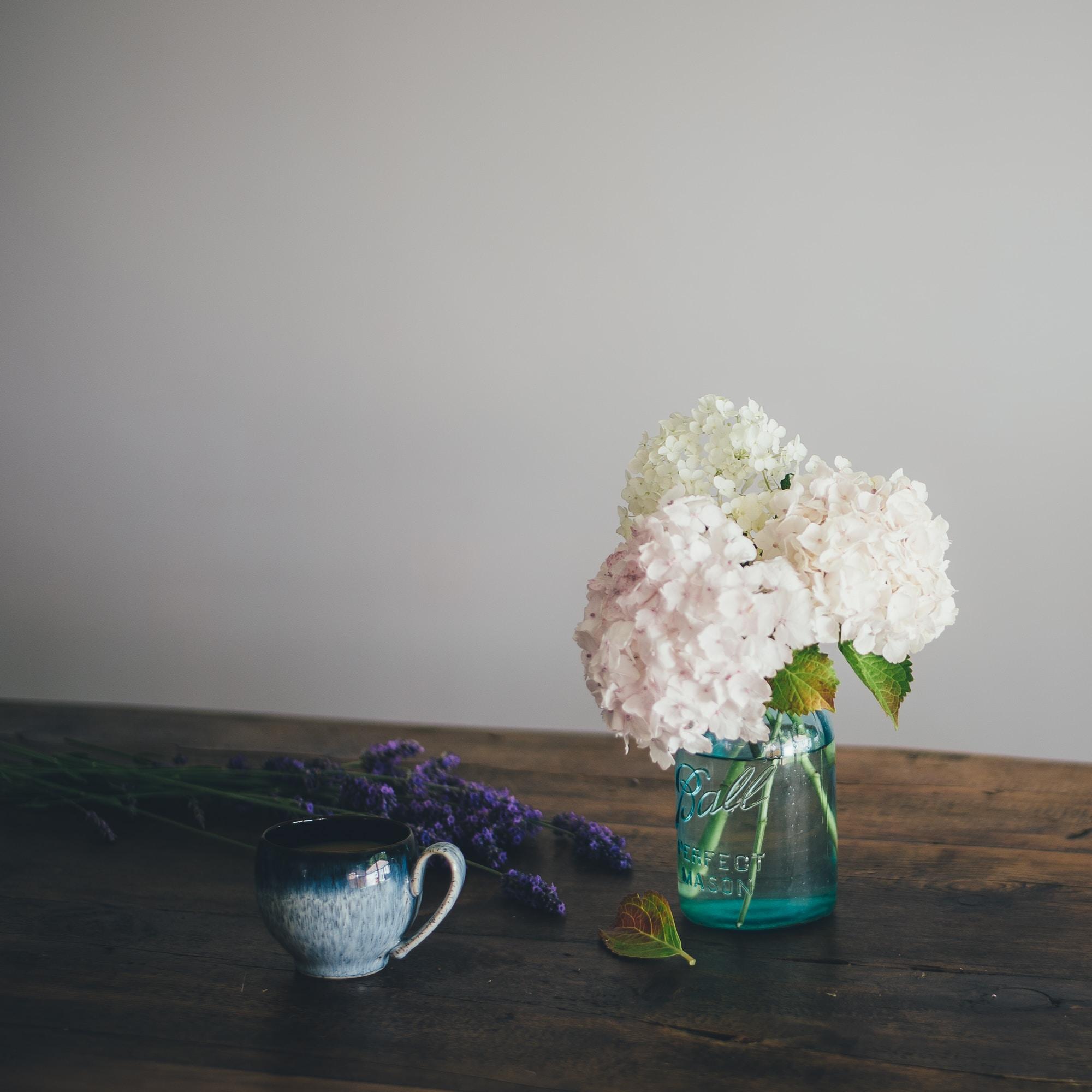 white flowers on green glass vase