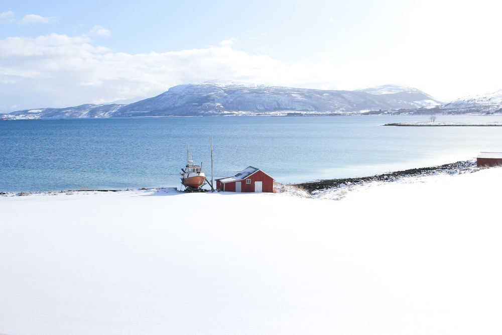 red house between sea and snow covered sand