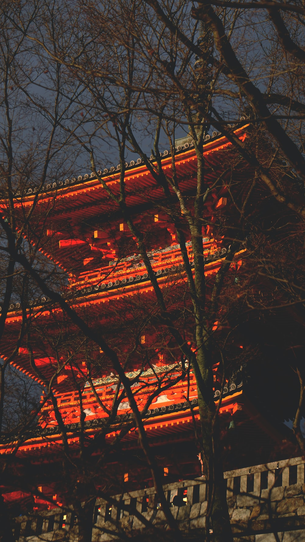 red temple surrounded by trees at nighttime