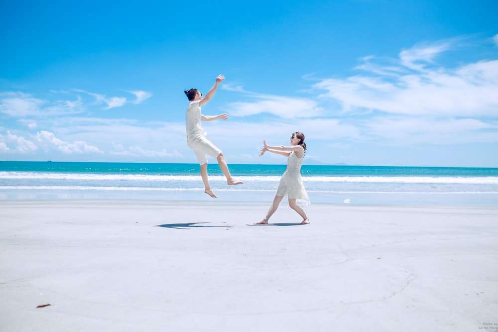 man and woman playing on white sand near seashore during daytime