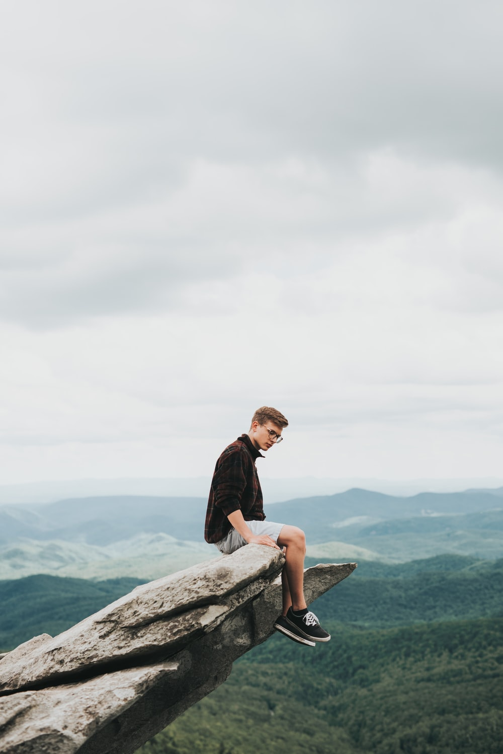 man sitting on the edge of stone