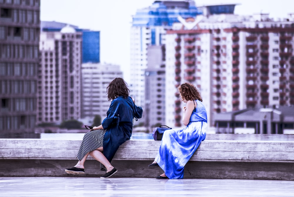 two women sitting on the roof