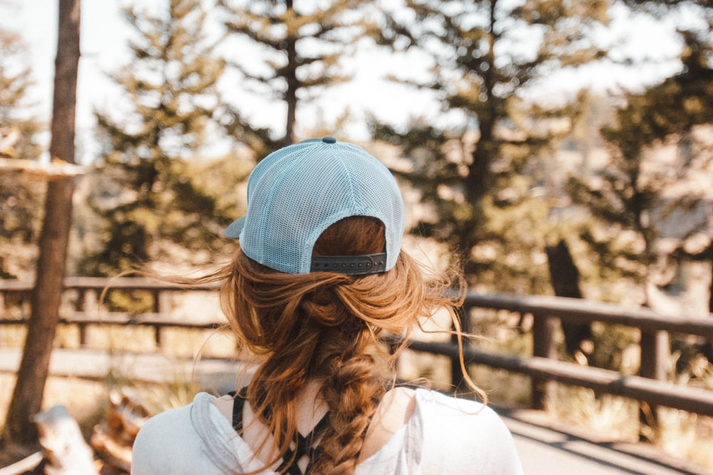 woman with blue trucker cap standing near brown wooden fence on road