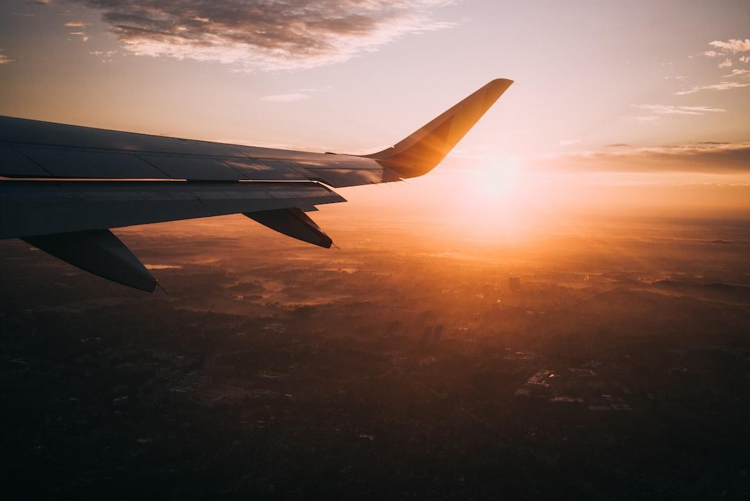 Airplane wing with sun on horizon creating an orange sky