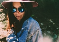woman in denim jacket wearing shades
