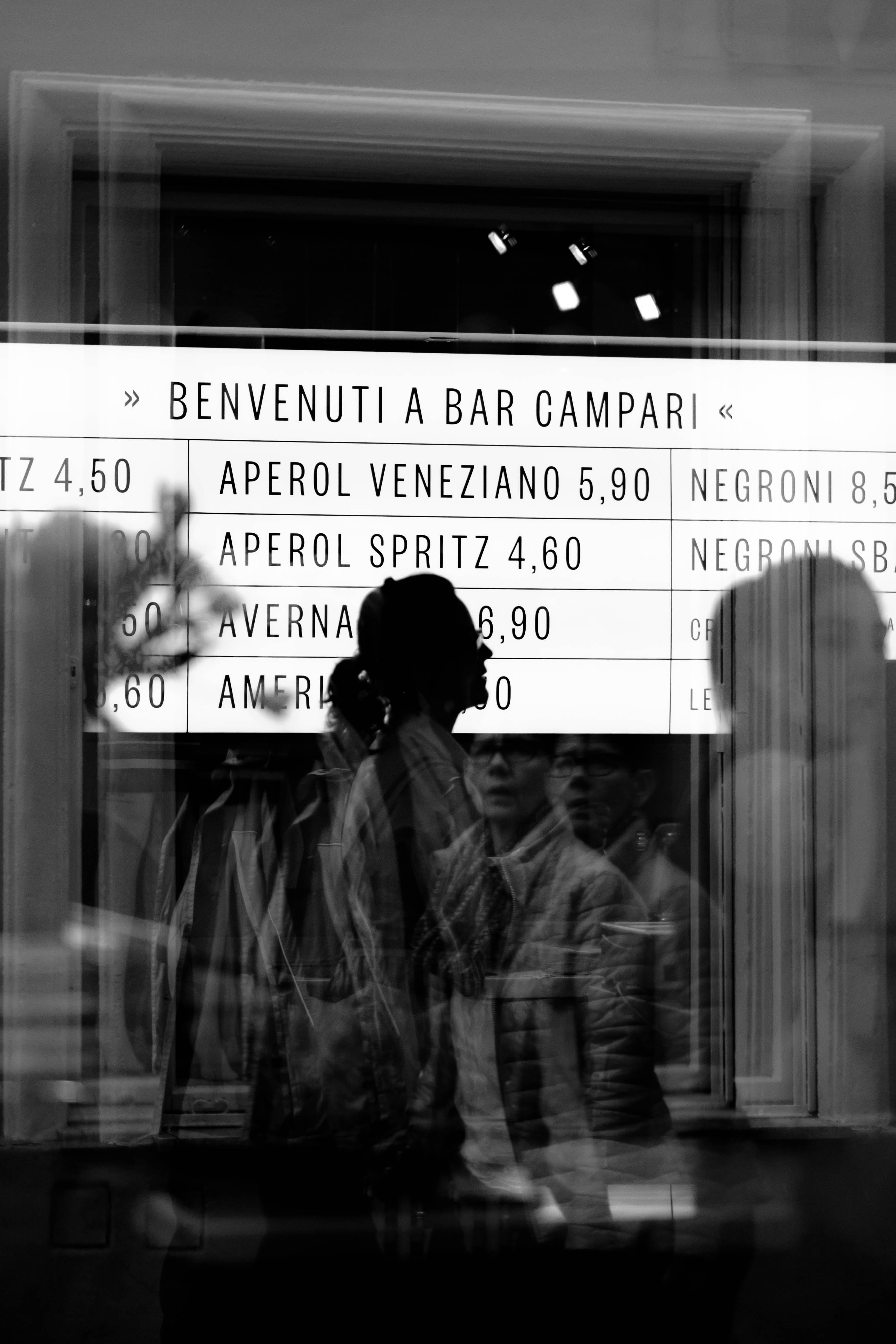 reflection of people from glass panel walking and passing signage in grayscale photography