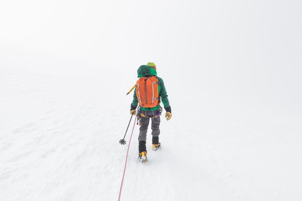 person holding ski pole on snow covered atmosphere