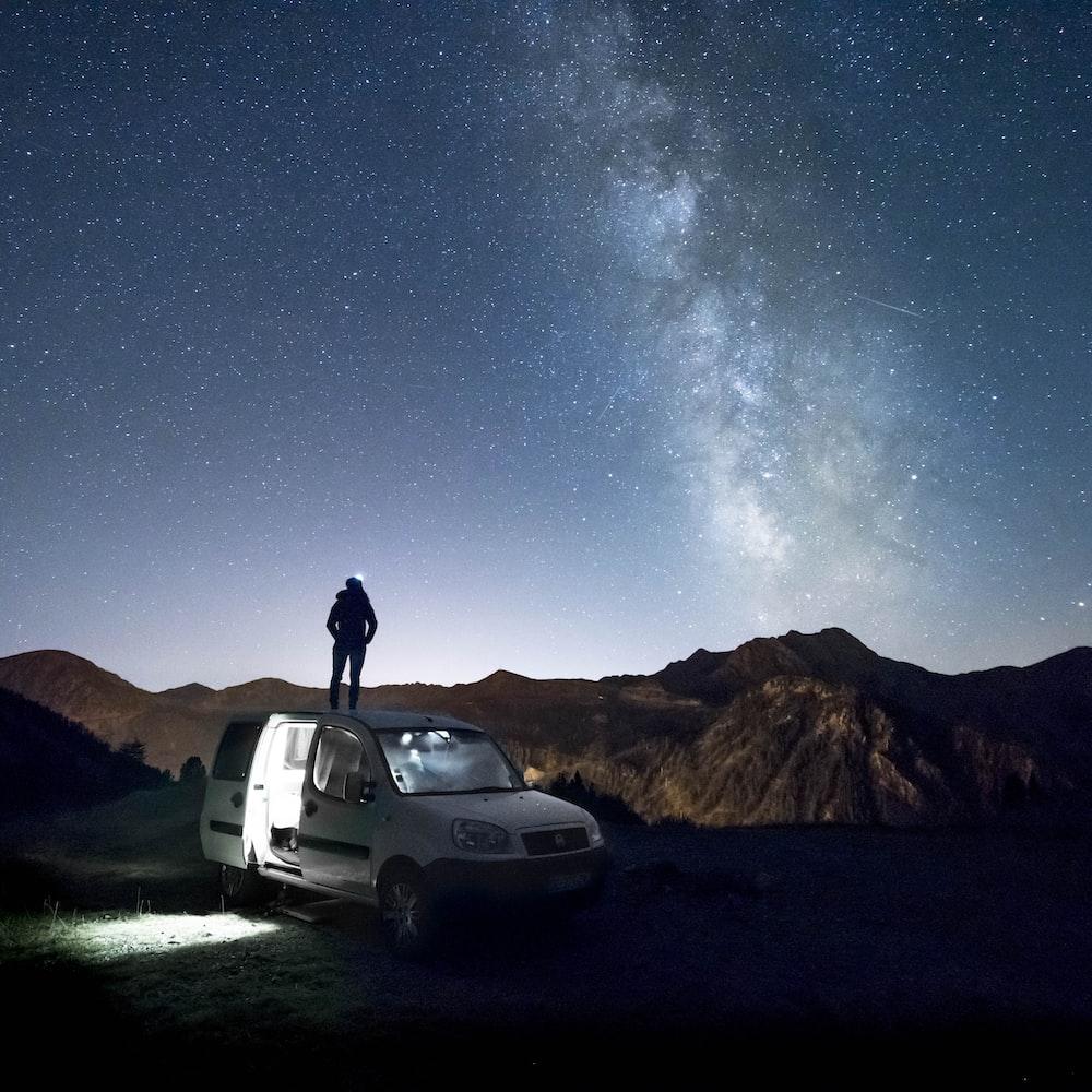 man standing on white minivan looking at mountain under milkyway