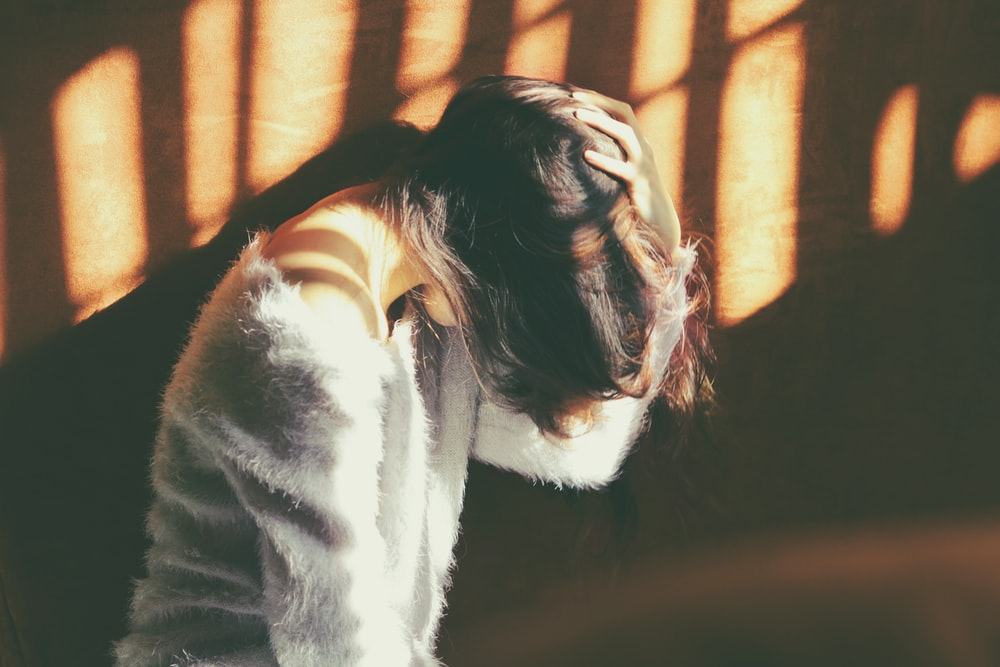 woman leans on wall in white fur jacket docking her head while holding it using her leaf hand