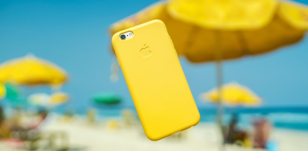 iPhone with yellow cover hanging on air