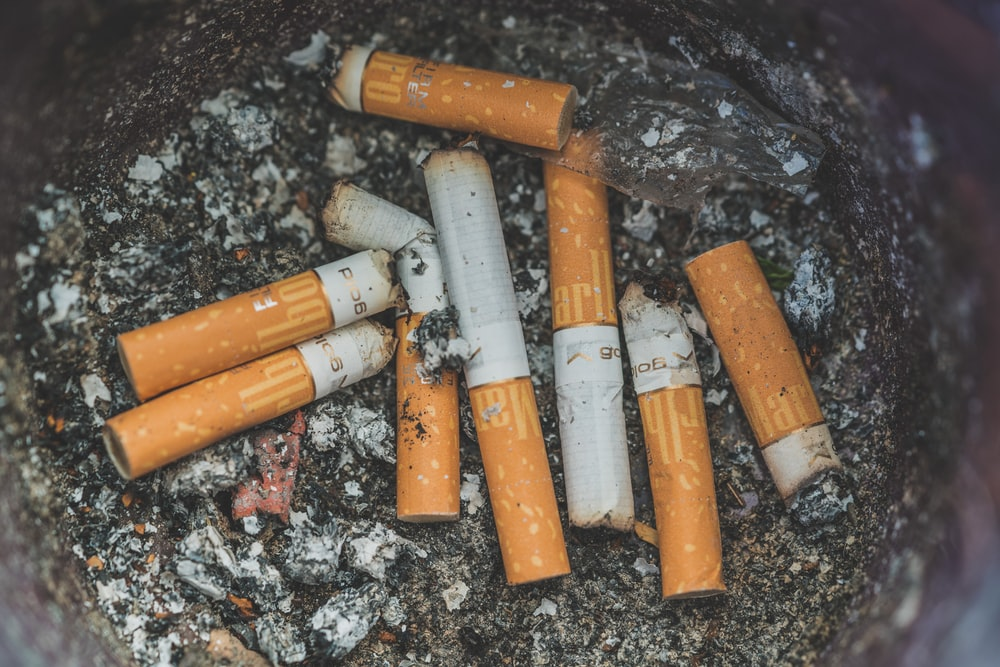 closeup photo of cigarette on ashtrays