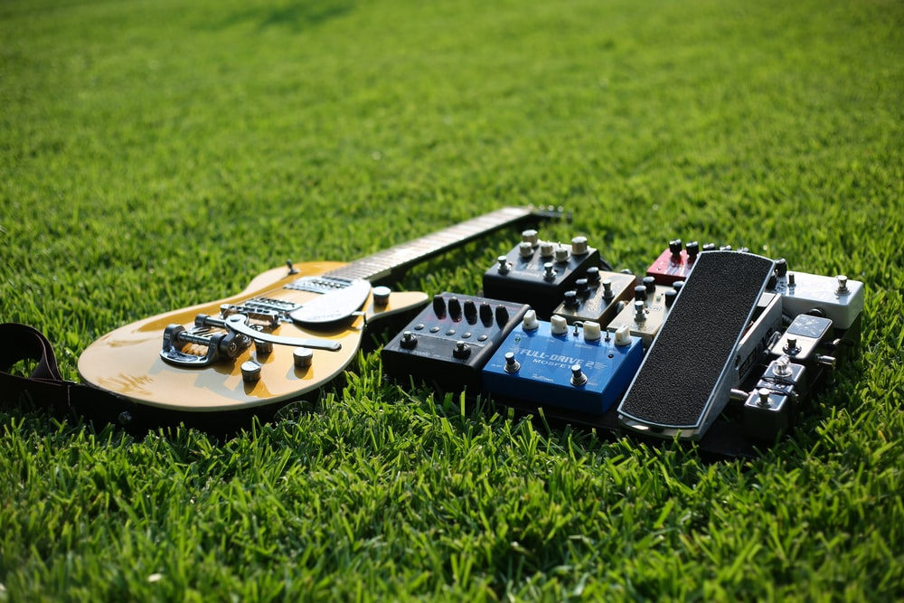 brown Les Paul-style electric guitar on grasses near guitar effects