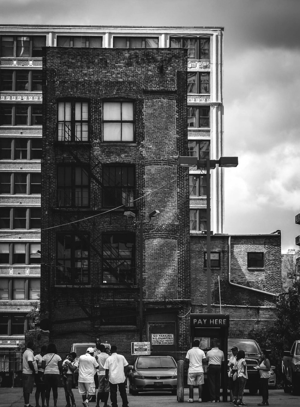 grayscale photo of people facing building