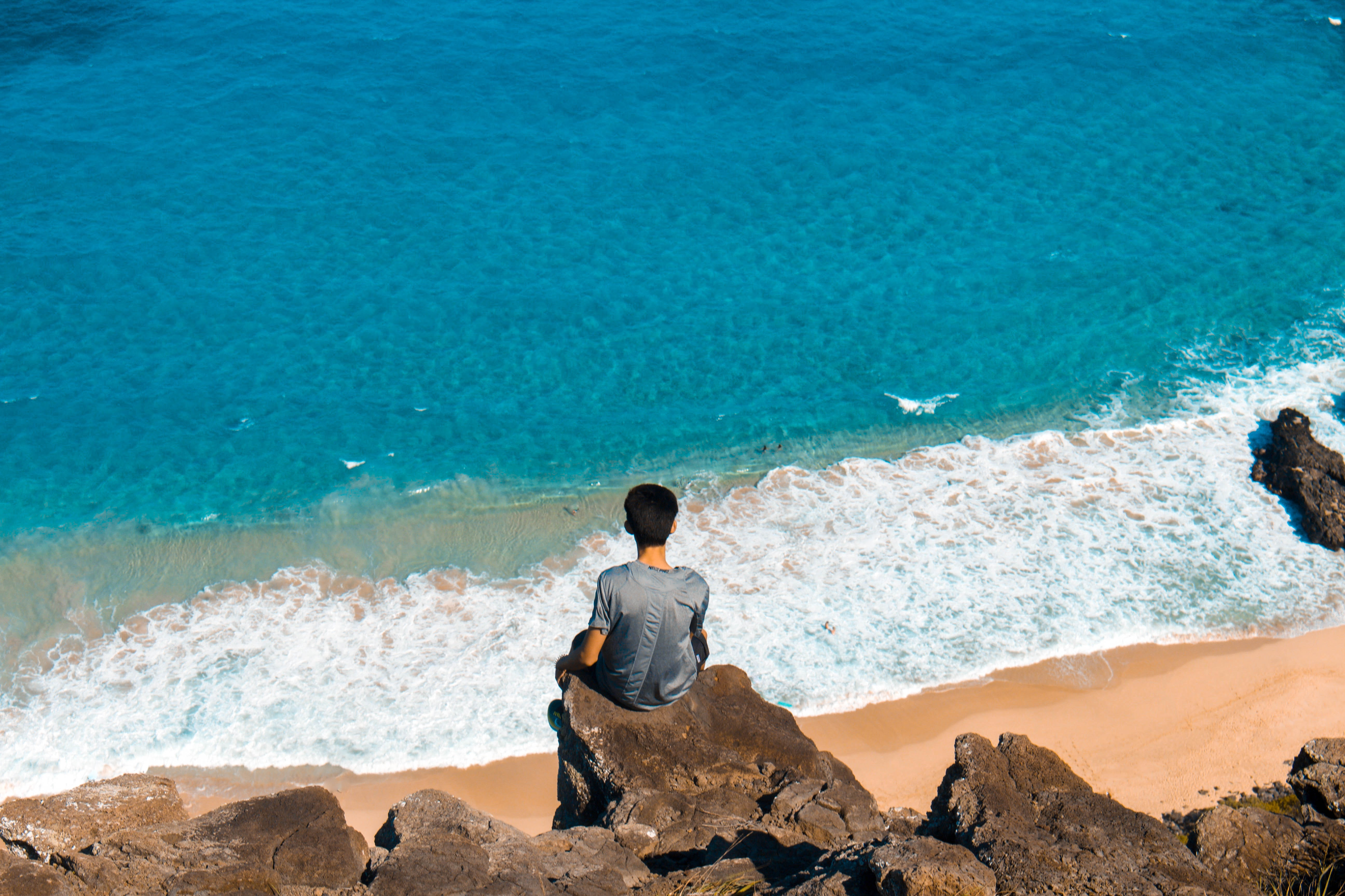 man sitting on top of cliff while looking on seashore