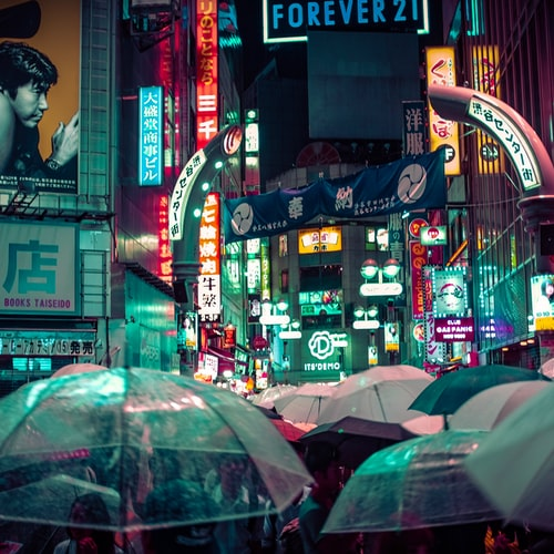 people holding umbrellas on a busy street at night lit by street lights and illuminated signs in Tokyo, Japan