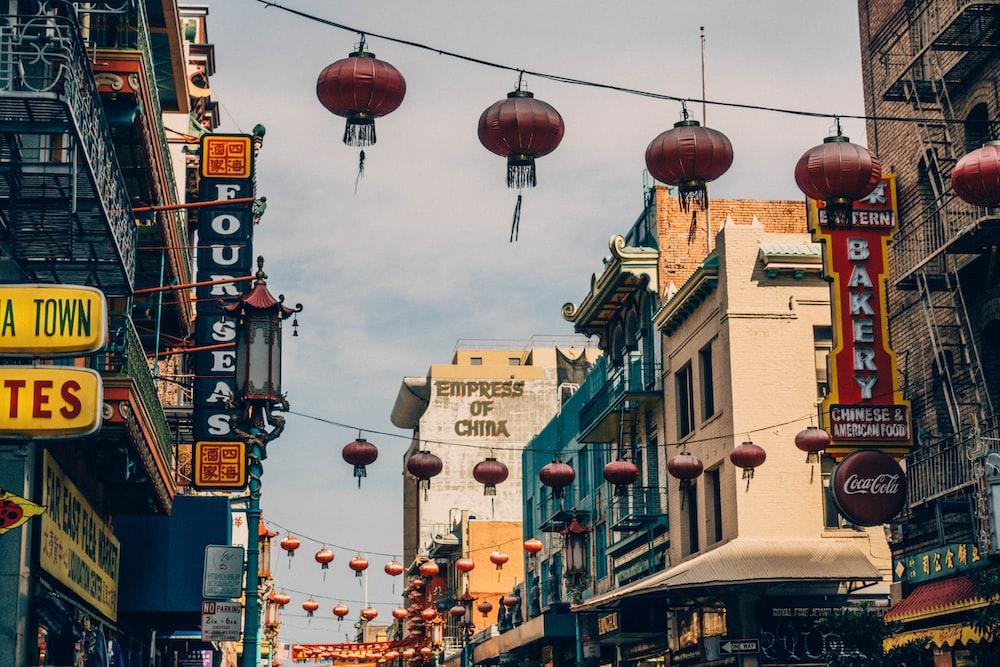 red Chinese paper lanterns hanging on street during daytime