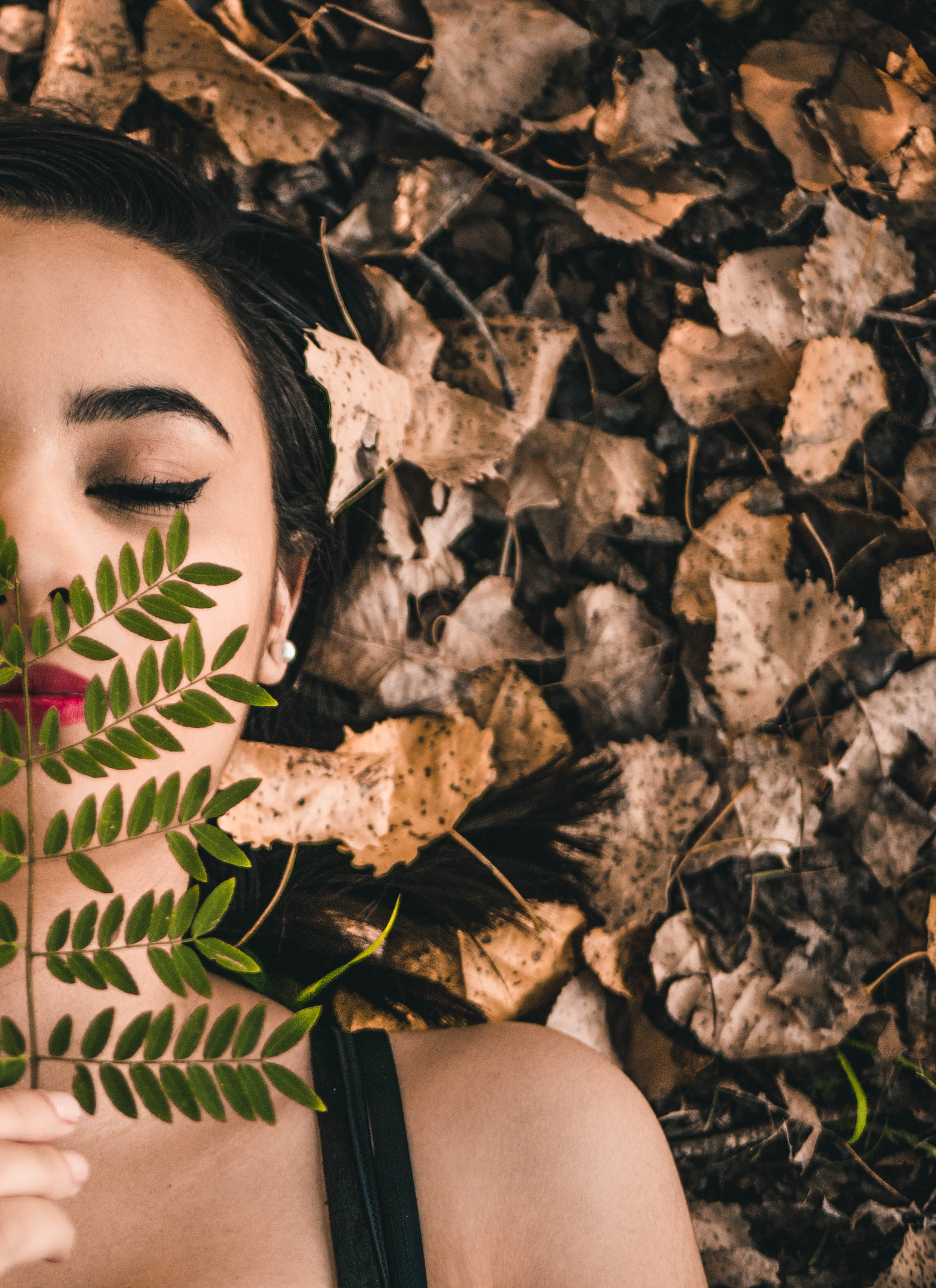 person holding leaf covering lips