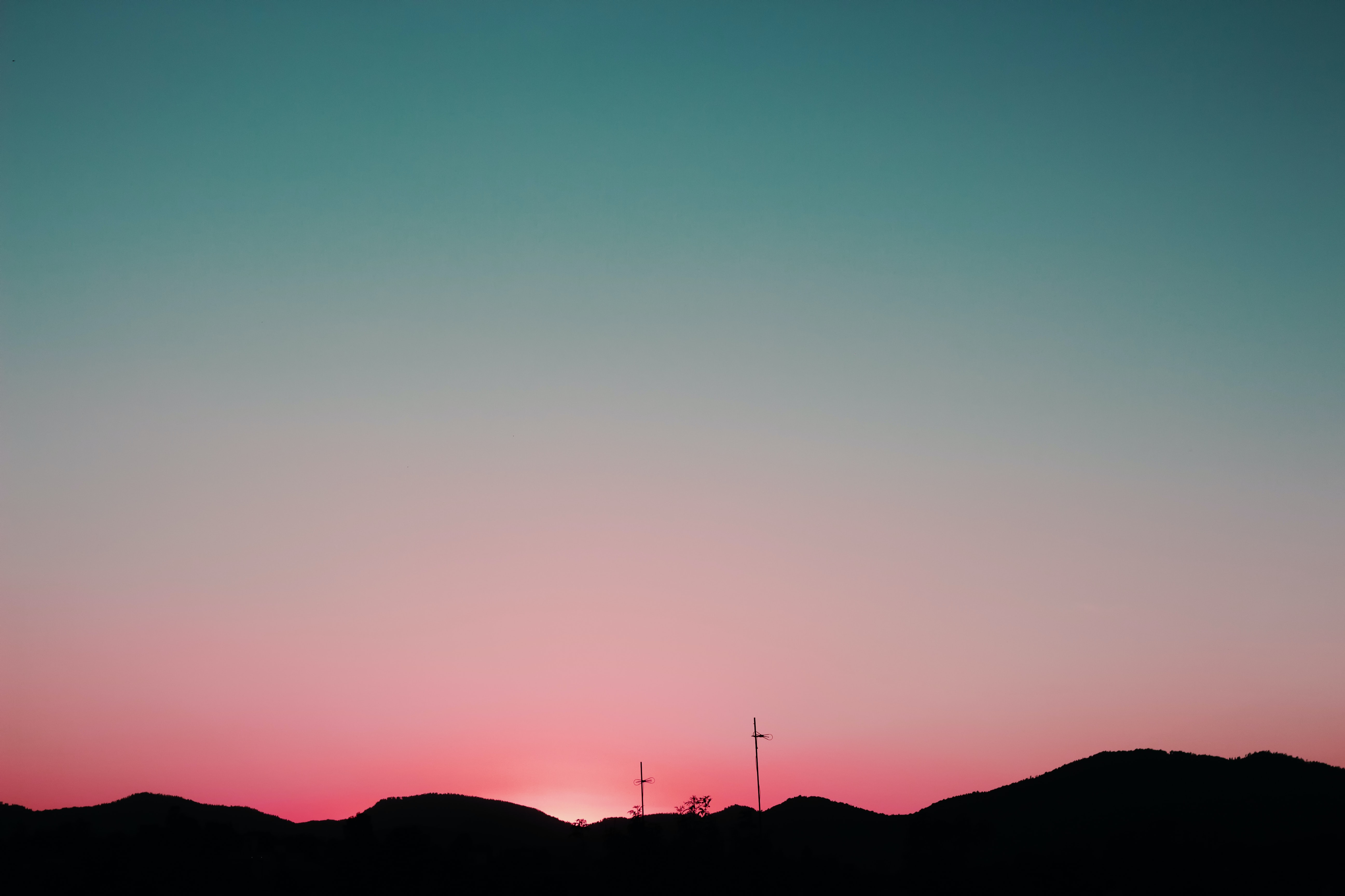 silhouette of mountains under pink and blue sky