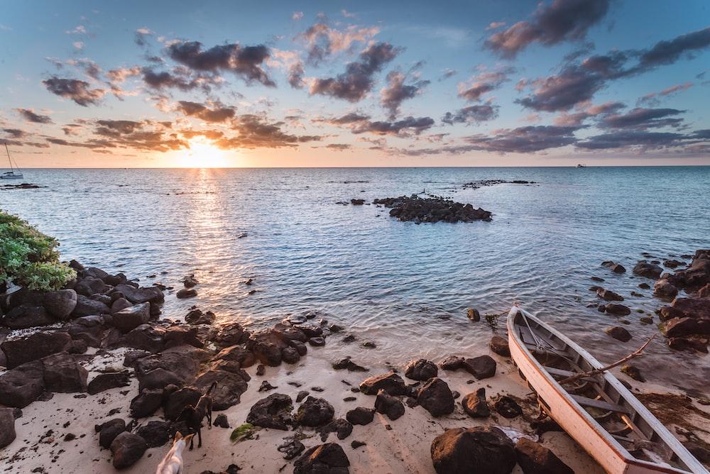 photo of white wooden boat on shoreline near rocks during sunrise