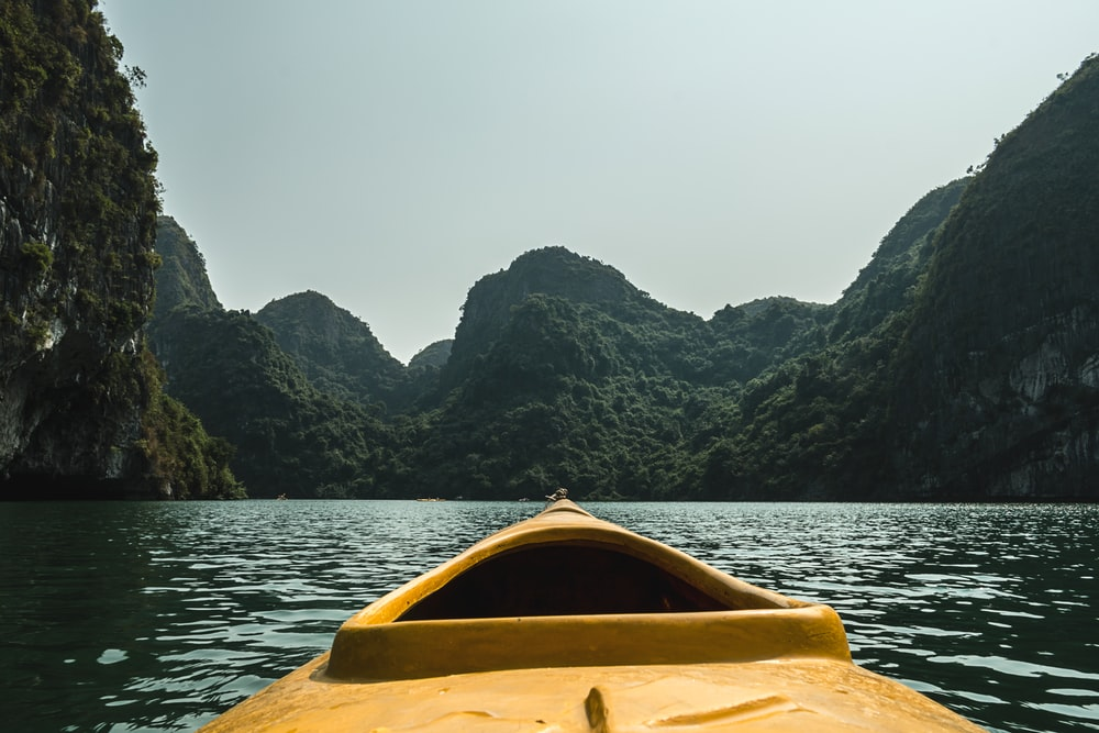 brown boat in the water surrounded by mountains