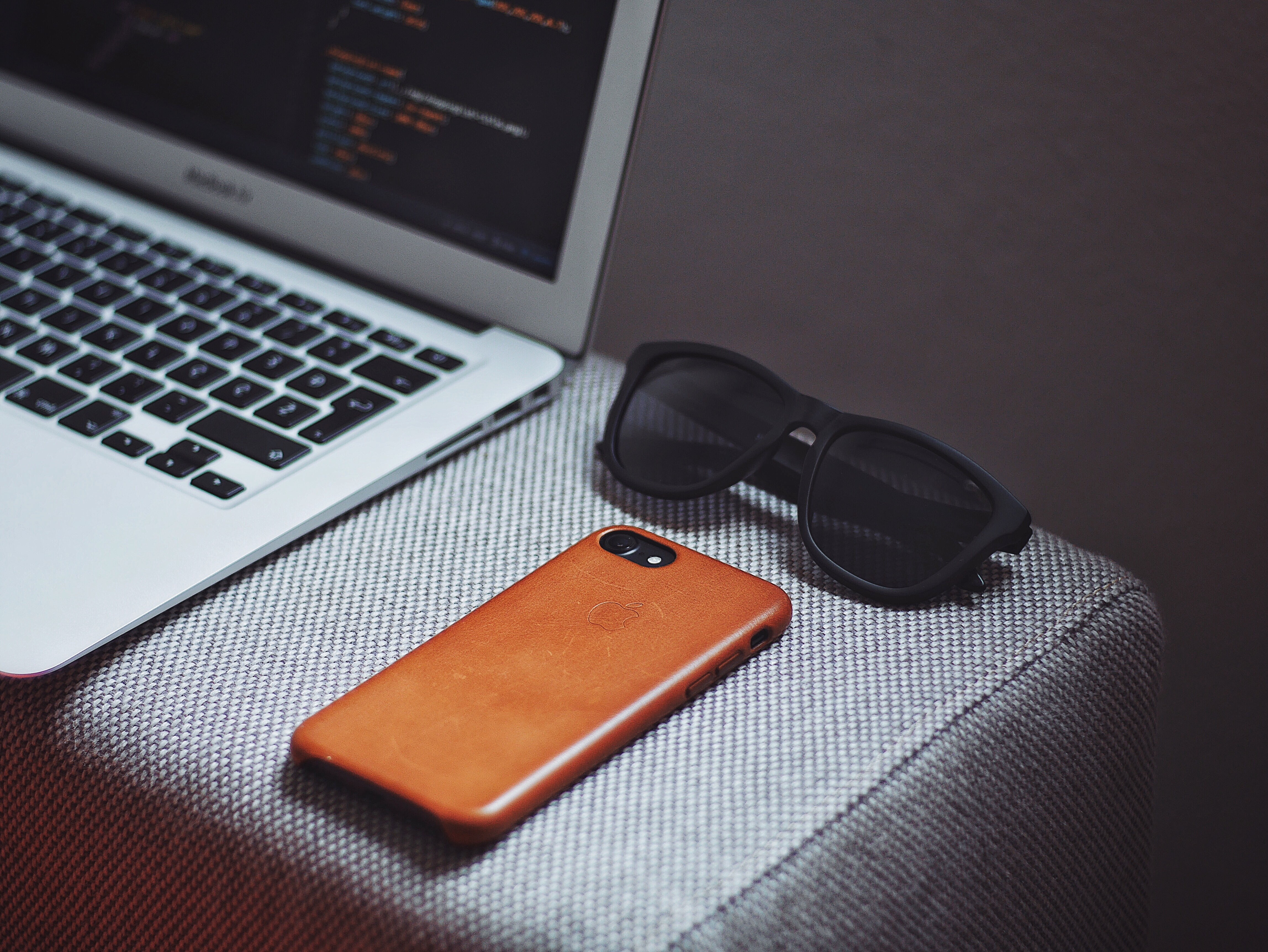 orange smartphone near black framed sunglasses beside MacBook Air