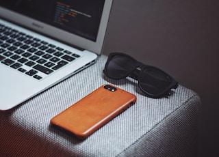 orange smartphone near black framed sunglasses beside MacBook Air