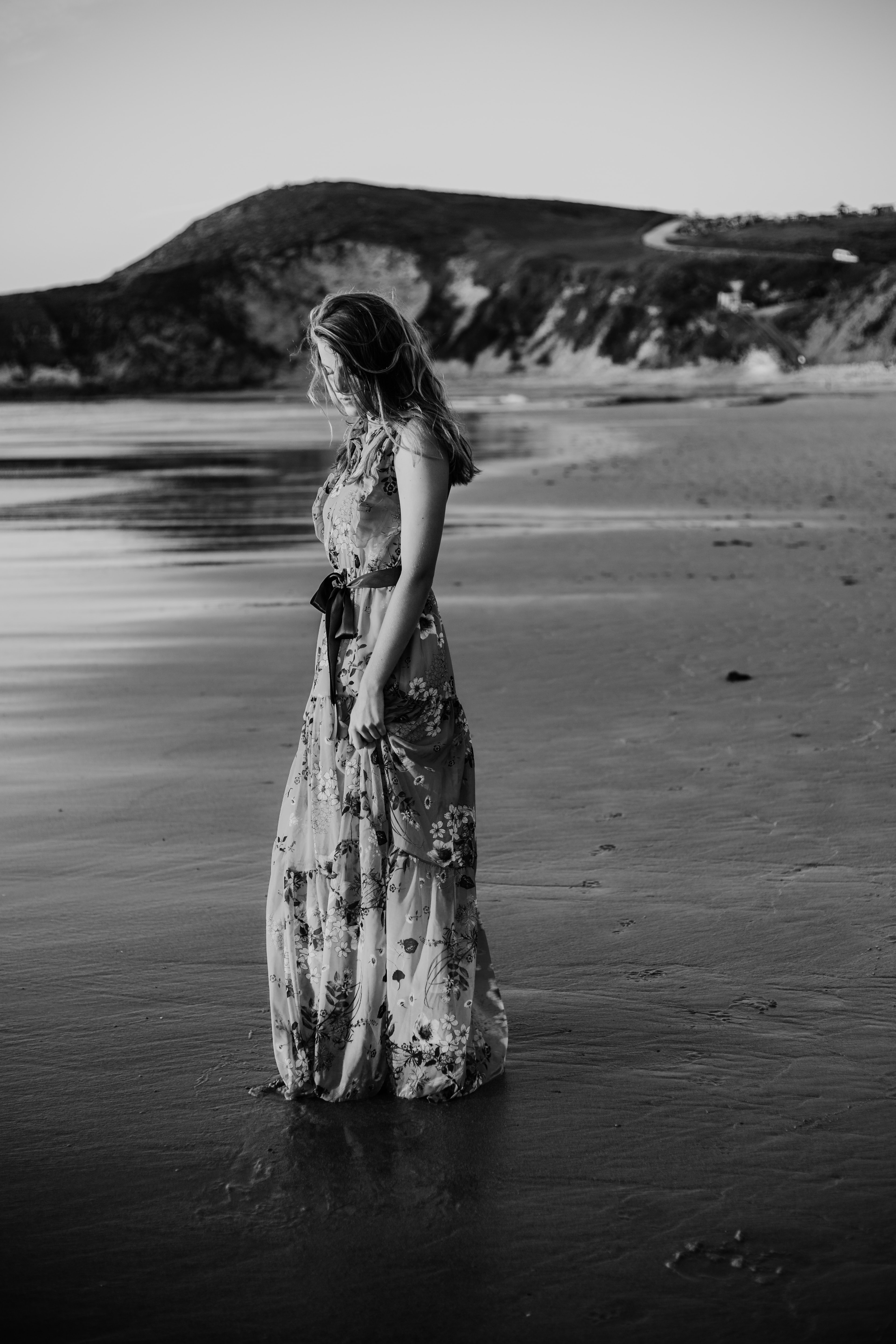 woman in floral long dress standing on seashore